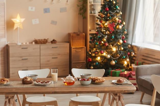 Hintergrundbild des gemütlichen wohnraums mit weihnachtsbaum und holztisch mit snacks im vordergrund, kopierraum