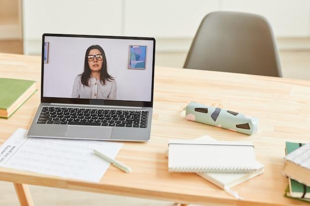 Hintergrundbild des hölzernen schreibtisches mit schulmaterial und laptop mit lehrerin, die videolektion oder online-klasse auf dem bildschirm stehend auf hölzernem schreibtisch mit schulmaterial, kopierraum gibt