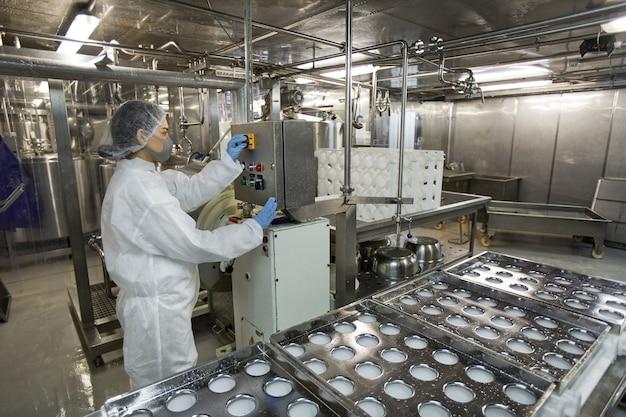 Hintergrundbild des industriellen förderbandes in einer sauberen lebensmittelproduktionsfabrik mit nicht erkennbaren arbeiterinnen, die maschineneinheiten betreiben, kopierraum