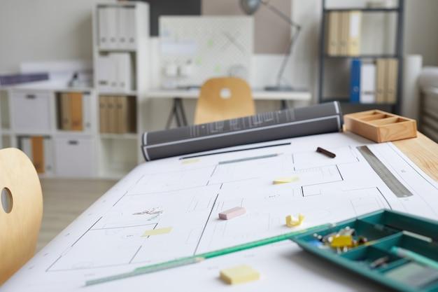 Hintergrundbild des leeren architektenarbeitsplatzes mit bauplänen und werkzeugen auf zeichentisch im vordergrund,