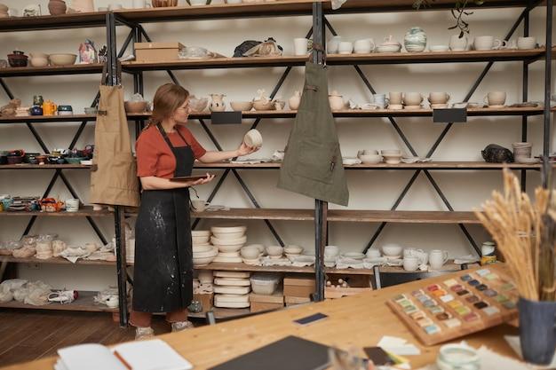 Hintergrundbild einer jungen handwerkerin, die keramik in regalen in der töpferwerkstatt organisiert, kopierraum