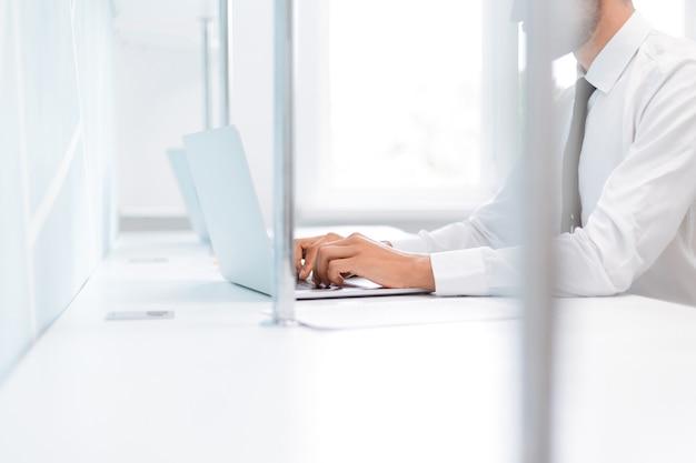 Hintergrundbild eines geschäftsmannes, der an einem bürolaptop arbeitet. foto mit kopienraum.