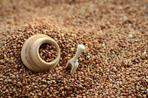 Hintergrundbild eines großen stapels des buchweizens, in dessen mitte ein kleiner krug und eine hölzerne spachtel für getreide liegen