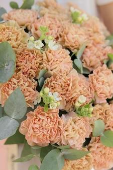 Hintergrundbild eines straußes aus cremebeigen nelken mit weißem oxypetalum und eukalyptus