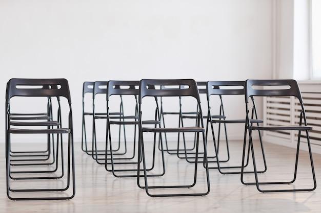Hintergrundbild in voller länge von schwarzen metallstühlen vor weißem hintergrund, eingerichtet für das publikum bei geschäftskonferenzen, kopierraum
