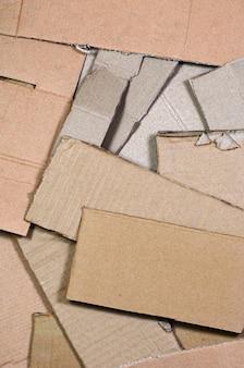 Hintergrundbild mit viel beige papppapier, das verwendet wird, um kästen für den transport von haushaltsgeräten und postpaketen herzustellen. kartonbeschaffenheit