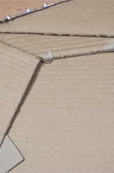 Hintergrundbild mit viel beige papppapier, das verwendet wird, um kästen für den transport von haushaltsgeräten und postpaketen herzustellen.