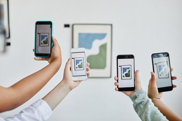 Hintergrundbild von händen, die smartphones in der galerie für moderne kunst halten und fotos von gemälden, digitaler welt, kopienraum machen