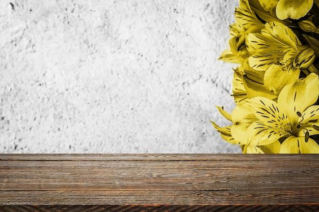 Hintergrundblumen auf einer strukturierten stuckwand und leeren holzbrettern im vordergrund