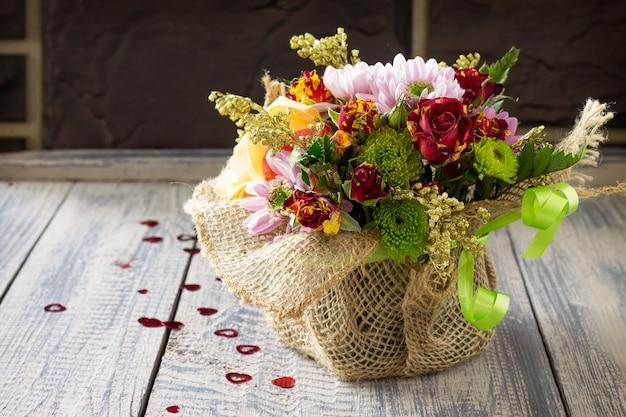 Hintergrundhochzeit oder valentinstag. korbstrauß aus rosen und chrysanthemen.