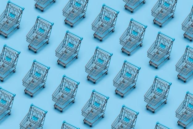 Hintergrundmuster. metall-einkaufswagen (spielzeug), geklont auf blauem hintergrund.
