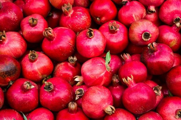 Hintergrundmuster von roten reifen granatäpfeln in den dunklen farben