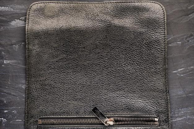 Hintergrundstruktur schwarzes leder. tasche der tasche mit einem schloss, nahaufnahme, eisen stilvolle schäbige reißverschlussschloss