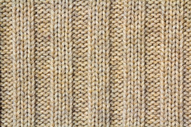 Hintergrundtextur des beige musterstrickstoffs aus baumwolle oder wolle nahaufnahme