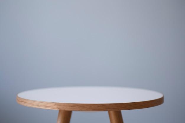 Hintergrundtisch runder couchtisch im innenraum vor dem hintergrund einer hellen leeren wand