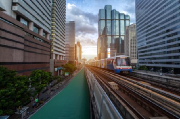 Hintergrundunschärfe des bts skytrain in bangkok mit abendsonnenuntergang