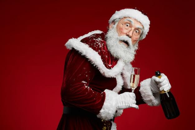 Hinterhältiger weihnachtsmann, der champagner hält