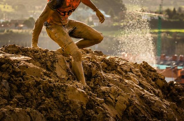 Hinterlaufender athlet, der die schmutzige pfütze in einem schlammrennläufer kreuzt.