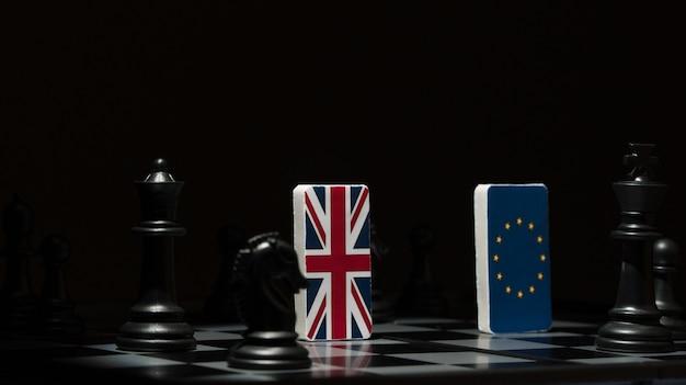 Hinterleuchtete im schatten figuren und flaggen der europäischen union und großbritanniens auf dem schachbrett