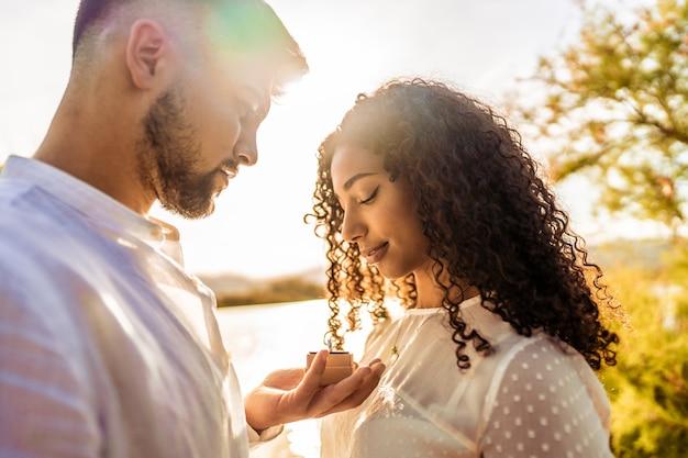Hinterleuchtete suggestive romantikszene eines jungen, schönen, verliebten paares aus verschiedenen rassen. hübscher kerl, der ihrer schwarzen hispanischen freundin den heiratsantrag macht, der verlobungsring in ihrer nähe zeigt showing