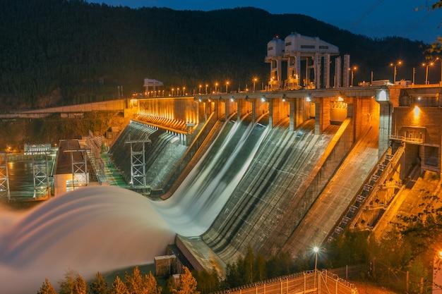Hinterleuchteter blick auf das wasserkraftwerk bei nacht. wasserablauf. bild auf langer dauer.