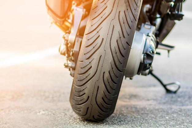 Hinterrad des sportmotorrades auf straße. motorrad in einer straße geparkt. freiheit und reisekonzept.