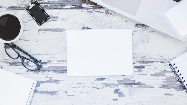 Hinweis und laptop in der nähe von briefpapier und kaffeetasse