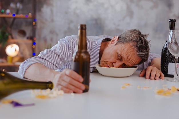 Hinweise auf alkoholismus. besoteter reifer mann, der in der schüssel liegt und flasche berührt