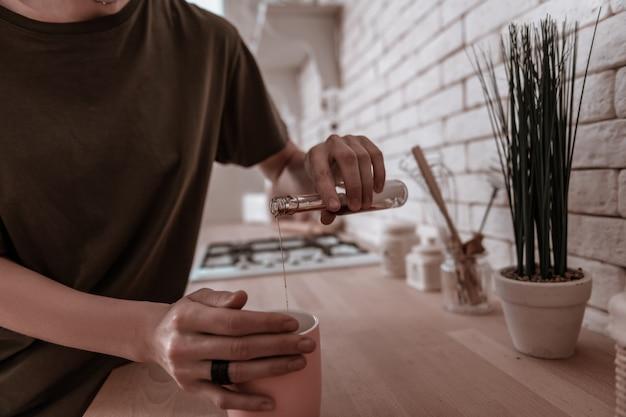 Hinzufügen von spirituosen. nahaufnahme einer frau, die ihrem morgentee etwas schnaps hinzufügt, während sie in der küche steht?