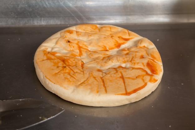 Hinzufügen von zutaten zu hausgemachter pizza