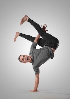 Hip-hop-typ führt breakdance-akrobatikelemente durch. man tanzt