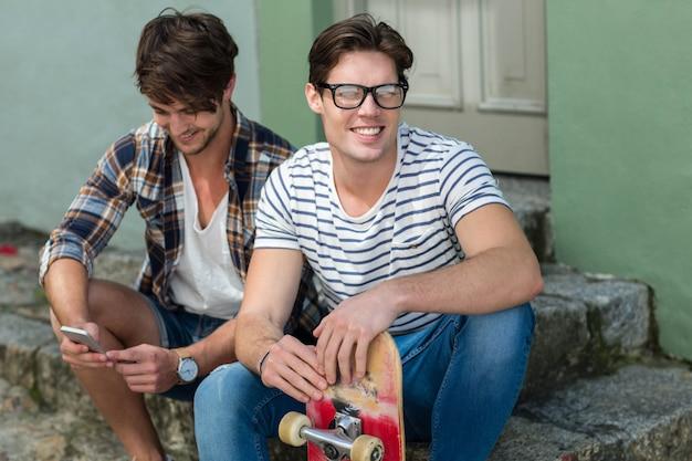 Hip männer sitzen auf stufen in der stadt
