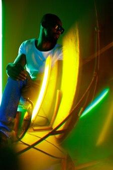 Hiphop. filmisches porträt eines stilvollen jungen mannes im neonbeleuchteten raum. helle neonfarben. afroamerikanisches modell, musiker drinnen. jugendkultur im party-, festival- und musikkonzept.