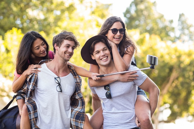 Hippe männer, die ihren freundinnen huckepack geben und selfie auf der straße nehmen