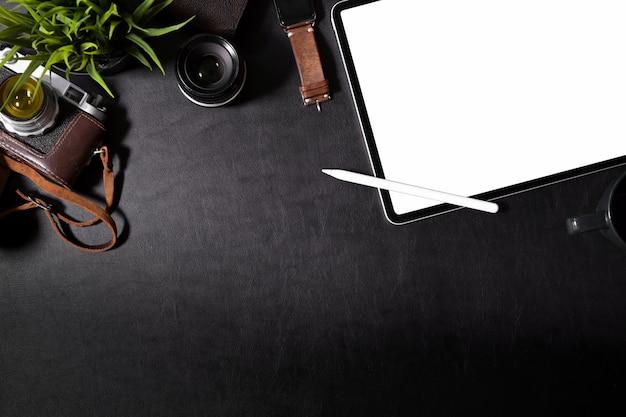 Hippie-arbeitsplatz mit weinlesekamera, filmen und tablette des leeren bildschirms auf schreibtisch