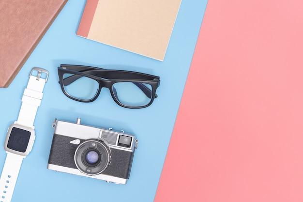 Hippie-bloggerreisegegenstände auf blauem rosa gelbem kopienraum für plakat und fahne