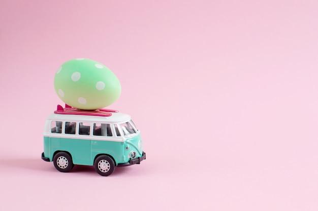 Hippie-bus mit bunten eiern ostern auf der dach-miniaturkleinwagen-fahne