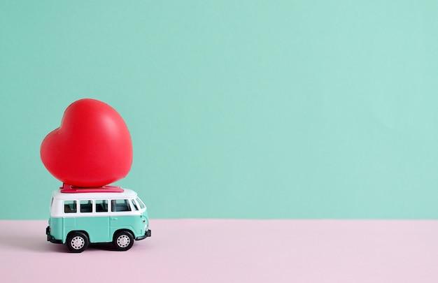 Hippie-bus mit rotem herzen auf dem dach-valentinsgruß-tagesminiaturkleinwagen-fahnen-liebesthema