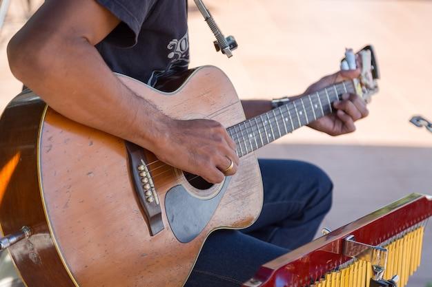 Hippie, der eine alte hölzerne gitarre im glücklichen moment mit unschärfehintergrund spielt