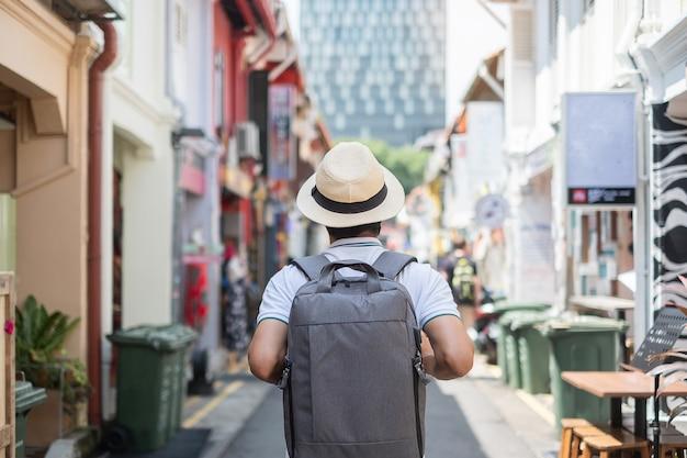Hippie des jungen mannes, der mit rucksack und hut reist