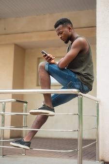 Hippie, ein junger mann, der einen smartphone verwendet