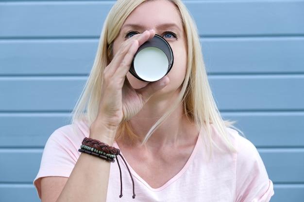 Hippie-frau, die boho-lederarmbänder an einem handgelenk trägt, das heißen kaffee von einem pappbecher zum mitnehmen trinkt, freepeople lebensstilkonzept.