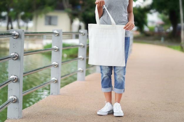 Hippie-frau, die weiße einkaufstasche hält