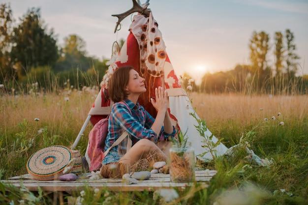 Hippie-frau in form eines schamanen sucht inspiration von mutter erde in einem wigwam in der natur.