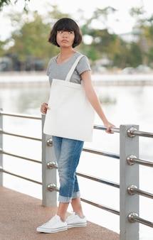 Hippie-frau mit weißer einkaufstasche im park