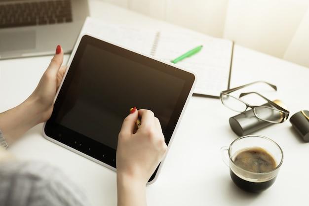 Hippie-frauenhände, die digitale tablette mit leerem leerem bildschirm für ihre textnachricht halten