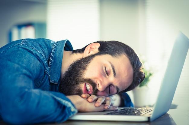 Hippie-geschäftsmann, der an seinem schreibtisch schläft