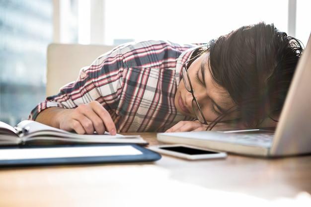 Hippie-geschäftsmann, der auf schreibtisch im büro einschläft