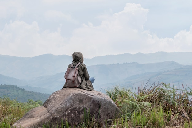Hippie-mädchen, das in felsigem des berges sitzt