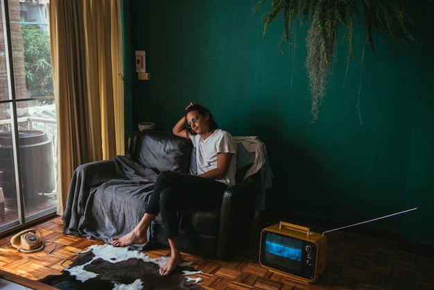Hippie-mann, der auf einem sofa sitzt